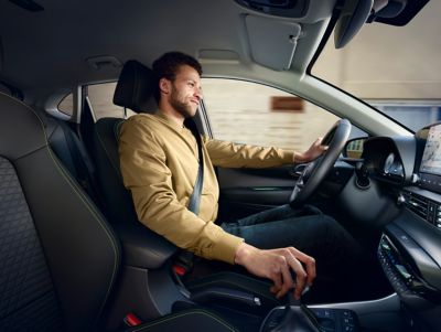 A man in a light brown sweatshirt driving the all-new Hyundai i20, co-driver's perspective