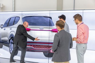 Four designers discussing the rear design of the new Hyundai SANTA FE Hybrid 7 seat SUV.
