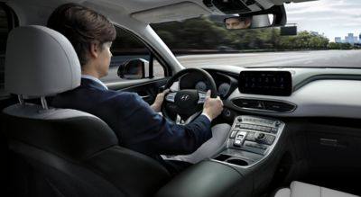 Interior view of the new Hyundai SANTA FE Hybrid 7 seat SUV showing a man driving down the highway.