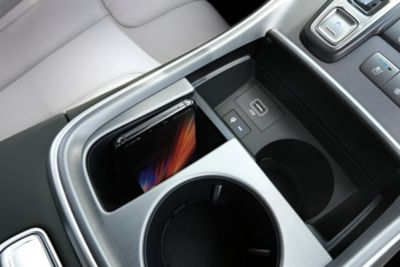 A close-up image of the upgraded wireless charging pad in the new Hyundai SANTA FE Hybrid.
